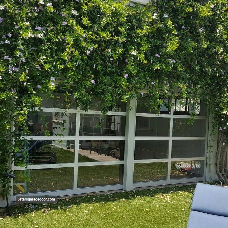 aluminum glass garage door in the green bushes